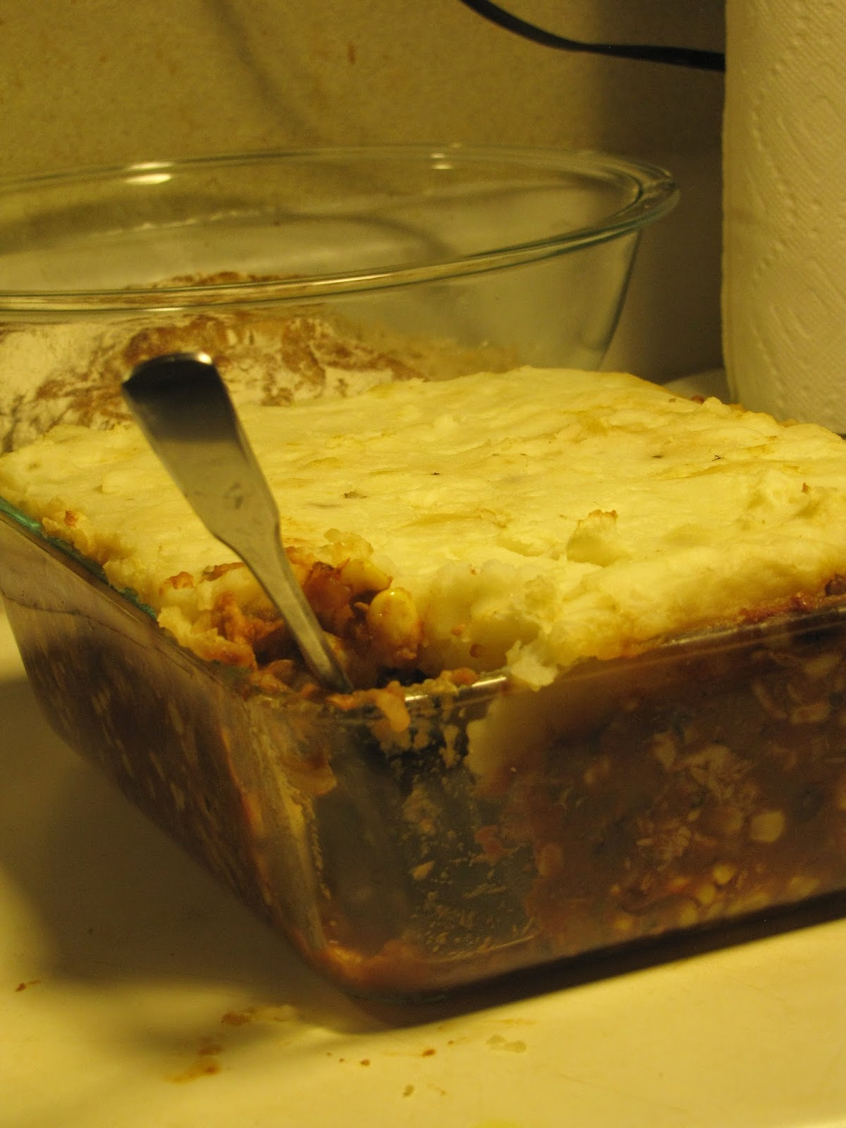 A fork in dish of just baked chicken chili pie, a spin on the traditional sheperd's pie