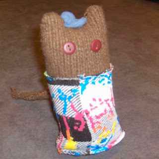 Cylindrical toy, cut out of brown sweater fabric with ears to suggest a cat's head. The eyes are two buttons and it wears a blue hat between its ears. The body is covered by a length of multicolored, graffiti-print sock material. The cat's tail, of brown sweater material, is visible in the back.
