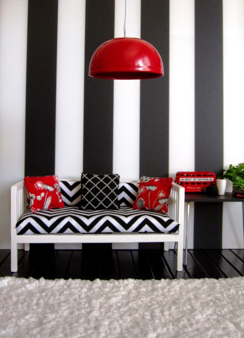 Modern miniature black white and red scene of a day bed with cushions next to a table displaying a model London bus, vases, books and a plant. A large red lightshade hangs from above and a white flokati rug is on the floor.