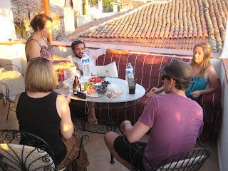 Enjoying the sunset while we eat under the large grape vine on the Taksiyarhis Pension balcony.