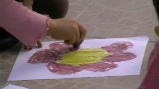 Szöveg: A nap kedvence a bordó virág. Kép: Közelkép egy készülő bordó virágról. A virágnak megvan a nagy sárga közepe, a gyermek meg a a hatodik szirmát festi éppen. Még egy szirom kifér oda.