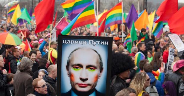 Ativistas LGBT seguram cartaz com montagem de foto do presidente da Rússia, Vladimir Putin, na qual ele aparece usando maquiagem (Foto: Cris Toala Olivares/Reuters)