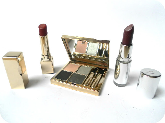 A picture of Clarins 121 Red Prodige, Clarins Joli Rouge Brilliant Perfect Shine Sheer Lipstick 14 Brilliant Grape and Clarins 06 Graphites Mineral Quartet