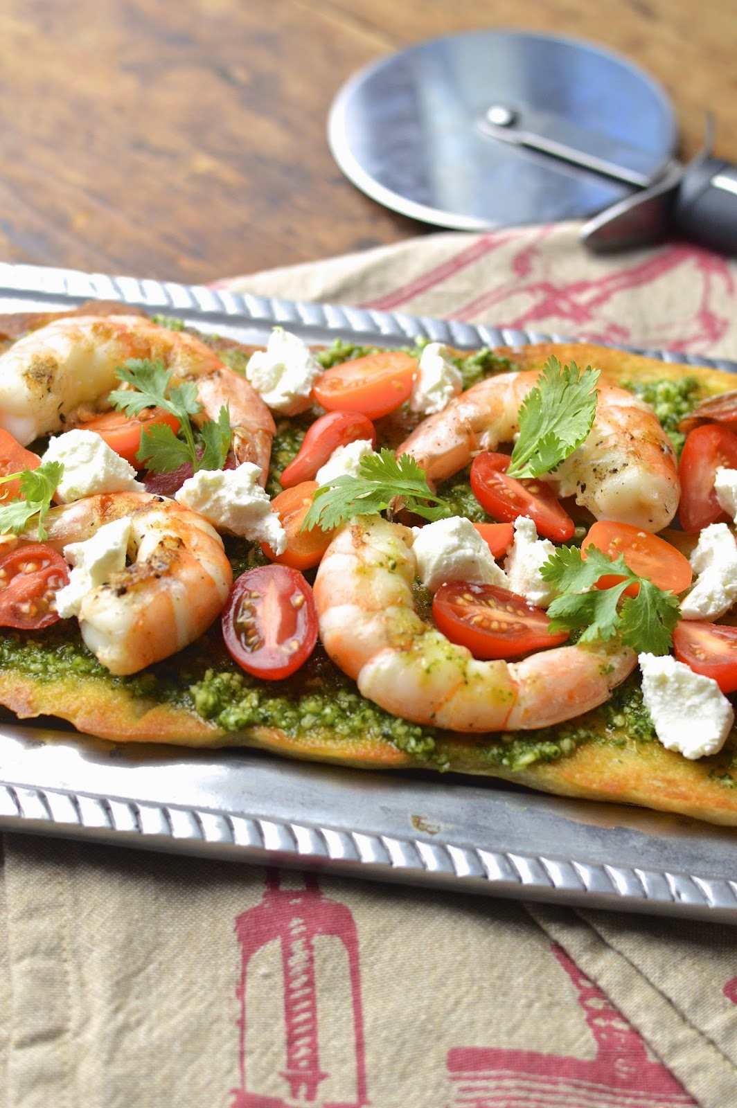 Bake pre-made pizza dough to make the perfect flatbread with grilled shrimp, cilantro pesto and goat cheese.