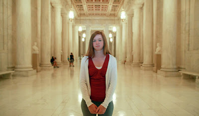 Photo of a 20-something white woman with sandy blond hair, standing in a big marble hallway