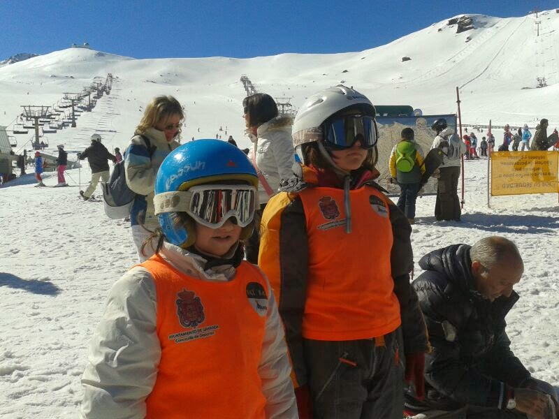 La imagen muestra a varios niños afiliados con los cascos, gafas y traje de nieve