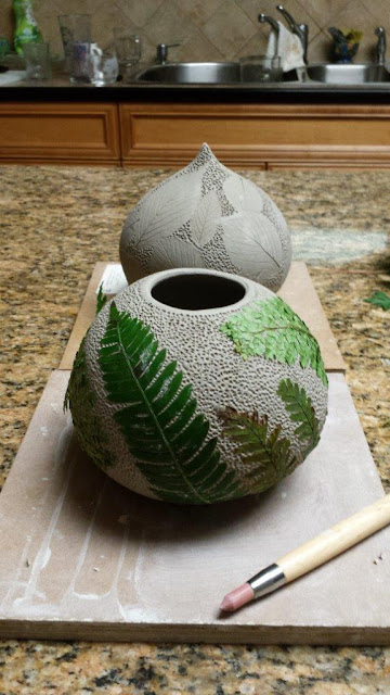 Ceramic pottery vessel with leaf imprints, this time fern fronds, in progress.