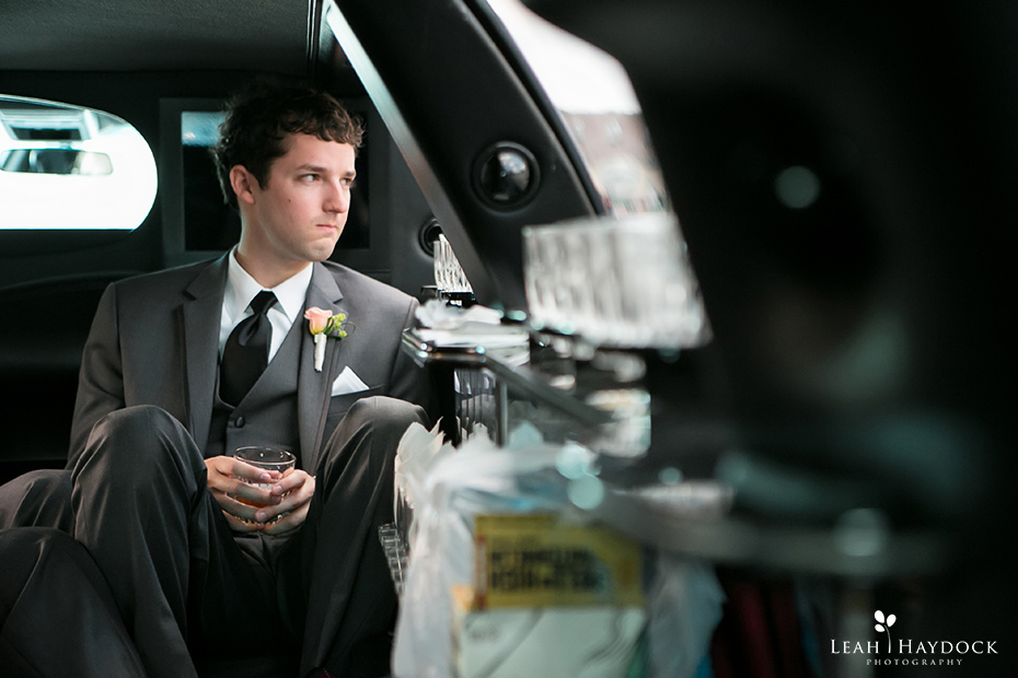 Groom sitting in limo with drink