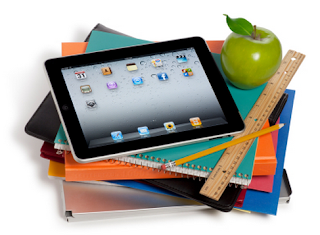 A stack of books and binders with a ipad on top