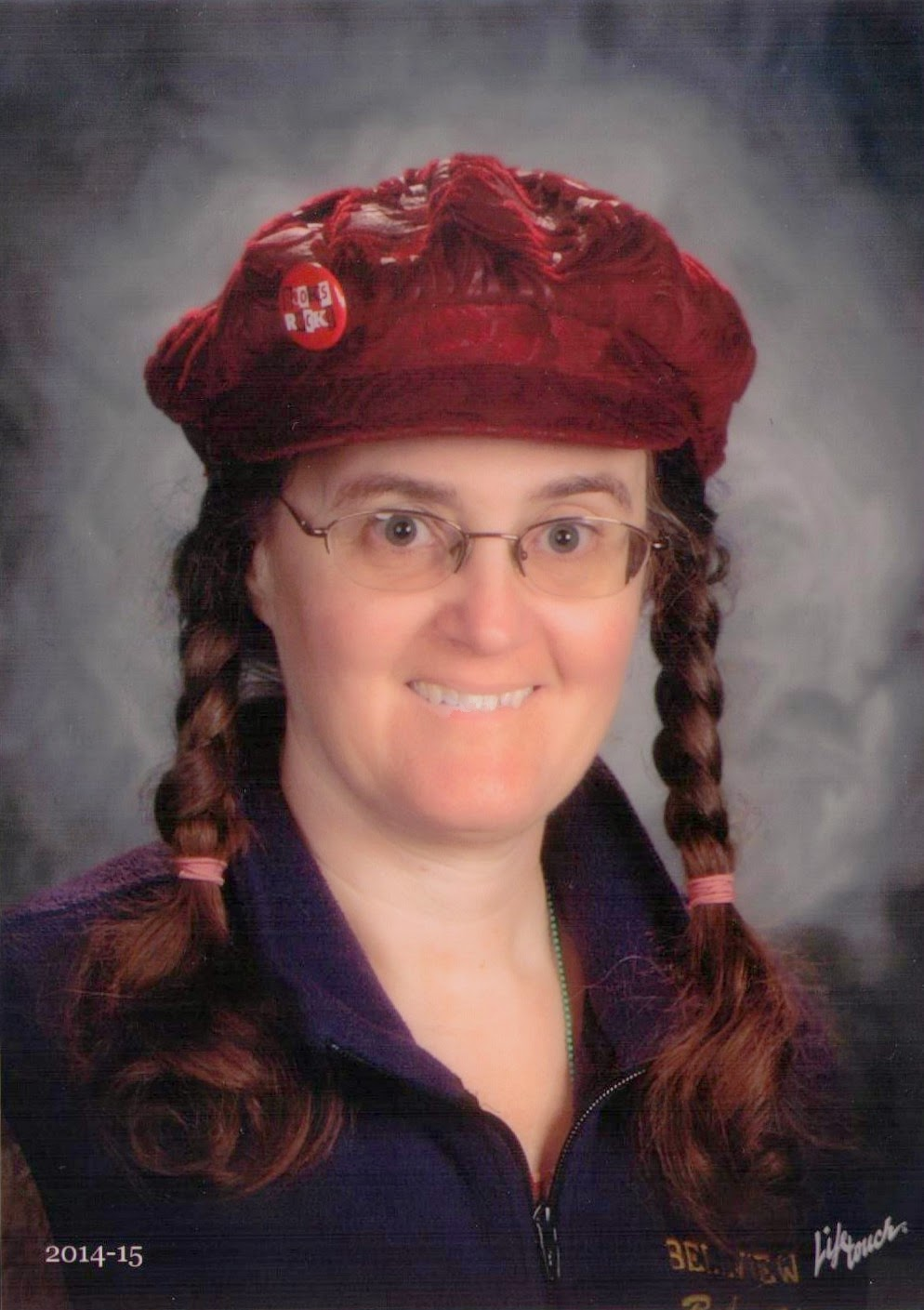 Head-and-shoulders photo of Cynthia M. Parkhill in blue vest, pigtails and red cap. A pin on her cap reads, Books Rock!