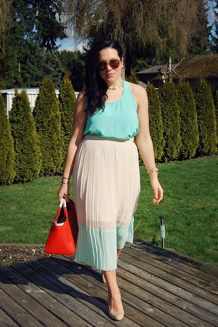 Mint silk tank and pleated maxi skirt with an orange Saffiano Furla bag.