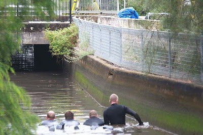 Police divers search the Meadowbank canal where body parts were found in a suitcase. Photo: Brendan Esposito