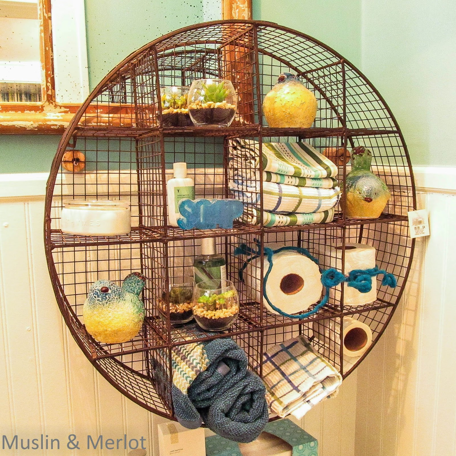 Round metal shelf utilized as a bathroom organizer.