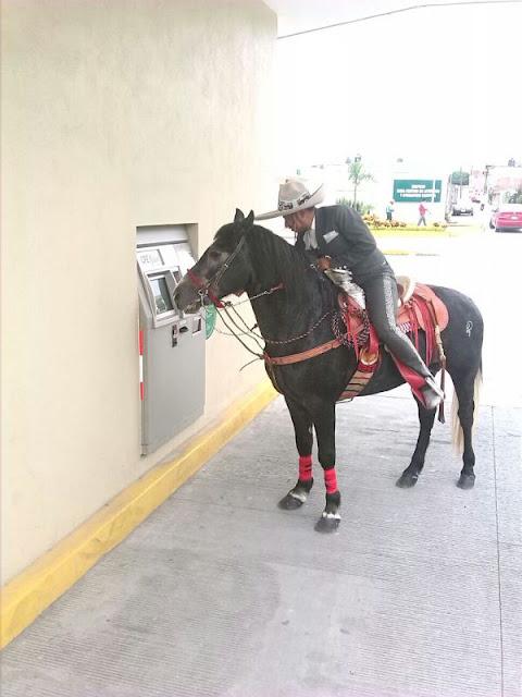 charro en caballo sacando dinero del cajero