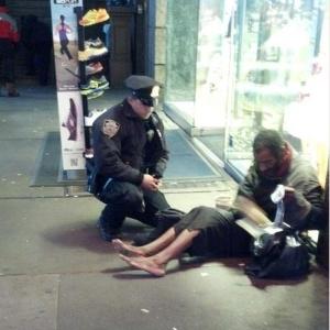 Policial doando botas para mendigo