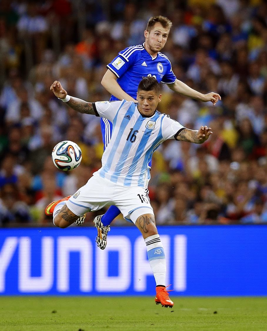 Argentina's Marcos Rojo (16) gets ahead of Bosnia's Izet Hajrovic to stop the ball during their group F World Cup soccer match at the Maracana Stadium in Rio de Janeiro, Brazil, Sunday, June 15, 2014.