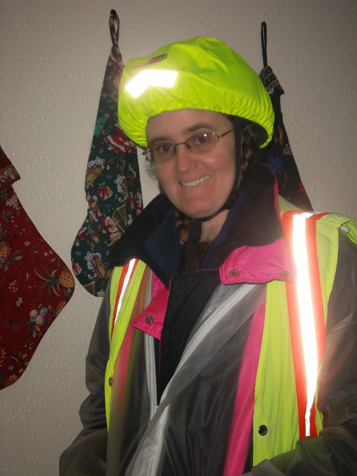 Cynthia M. Parkhill in bright-green bicycle helmet cover, reflective vest, white-clear plastic rain jacket over black jacket and blue vest.
