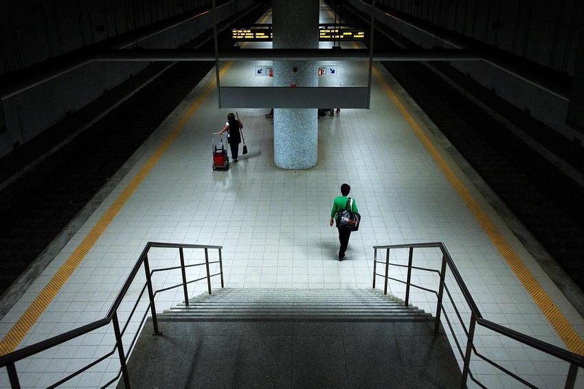 Foto na estação de Espinho. Em primeiro plano as escadas, centradas na imagem e a seguir, ao meio, a plataforma de espera com as linhas uma de cada lado. Uma mulher a caminhar e outra com o carro das limpezas.