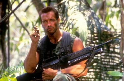 """Cette image est tiree du film de science-fiction americain """"Predator"""" realise par John Mc Tiernan en 1987 avec dans le role titre Arnold Schwarzeneger, l'un des plus fameux acteurs de films d'action de toute l'histoire de cinema. Schwarzeneger fut un immense culturiste, avec cinq titres de Monsieur Olympia, avant sa carrière hollywoodienne et un homme politique après, devenant meme gouverneur de l'Etat de Californie. Le film Predator, l'un des meilleurs dans lesquels joue Arnold Schwarzenegger raconte l'affrontement au sein d'une jungle inhospitaliere d'un groupe de mercenaires avec une creature extraterrestre, venue sur Terre pour faire une espece de safari dont les humains chasses sont les trophees. Sur la photo on peut voir Schwarzenegger qui pose de face un cigare dans sa main droite près de la bouche. Il porte un gilet aux couleurs kaki pour mieux se dissimuler et son avant-bras droit posé sur sa jambe gauche repliee soutient une enomre fusil d'assaut. Le gilet laisse paraitre les bras musculeux de l'acteur. Son visage arbore une barbe de plusieurs jours ainsi que des marques noirs destinees probablement a mieux passer inaperçu. Les cheveux sont tailles en brosse. A l'arrière plan, on distingue une végétation luxuriante que l'on devine celle de la jungle. Cette image extraite d'un très bon film que Le Marginal Magnifique adore accompagne le poeme """"Guerilla"""" dans lequel le grand poete qu'est Le Marginal Magnifique compare la vie sociale a une guerilla constante puisque les gens sont souvent betes et malintentionnes et qu'il faut du coup etre sans arret sur ses gardes. Un bon poeme du Marginal Magnifique, tout a fait dans son style avec un theme recurrent chez le grand auteur."""