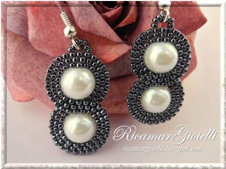 Orecchini Infinito realizzati con perle 8 mm e decorati con una doppia onda in brick stitch di rocailles 15/0 a formare il simbolo dell'infinito