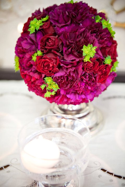 ann arbor wedding florist, detroit, south east Michigan wedding florist, red roses, purple carnations, green buplerum, silver candlestick , candle,sweet pea floral design