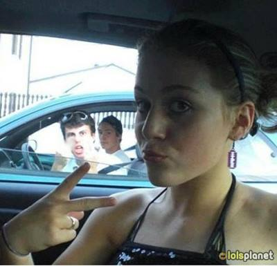 girl making duck face in car and a guy is showing a middle singer , photo bomb , best answer to duck face , cute girl making duck face