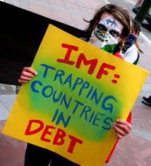 man holding play card saying imf-trapping countries in debt