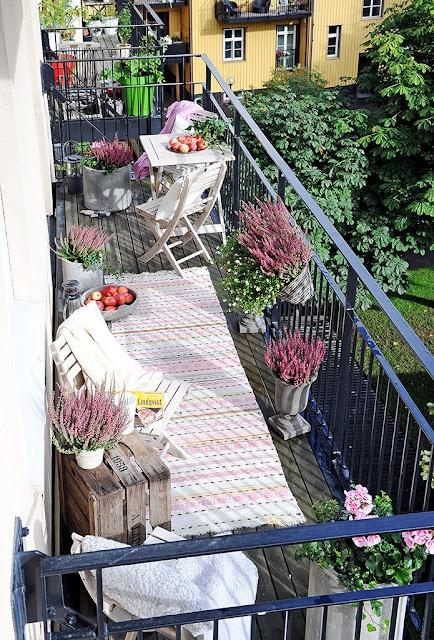 растелянный плед на балконе и горшки с цветами