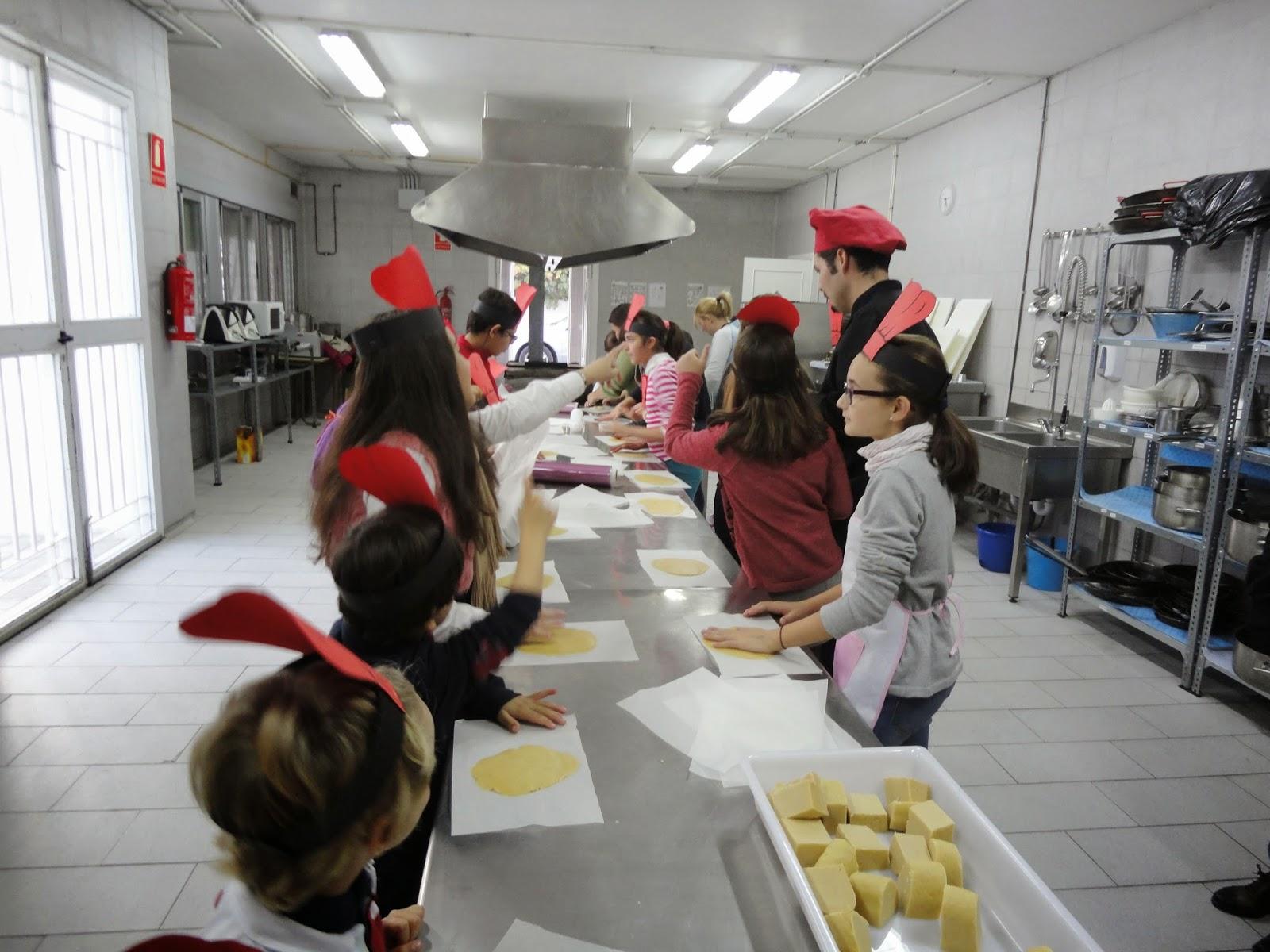 la imagen muestra un salón con una gran mesa de cocina, el chef y los niños