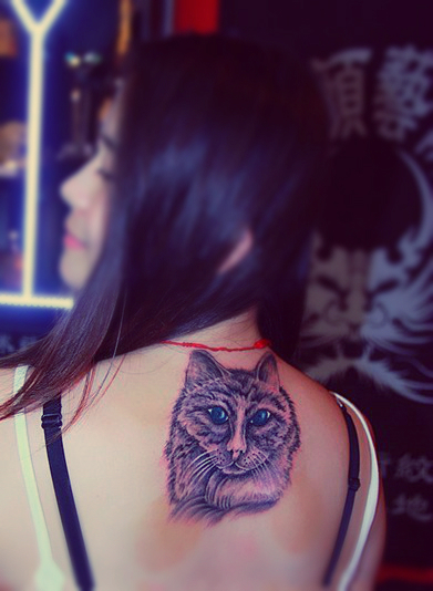 A vivid cat tattoo on the back