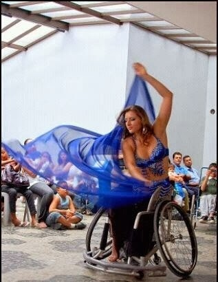 woman in a wheelchair doing belly dance performance with blue scarves