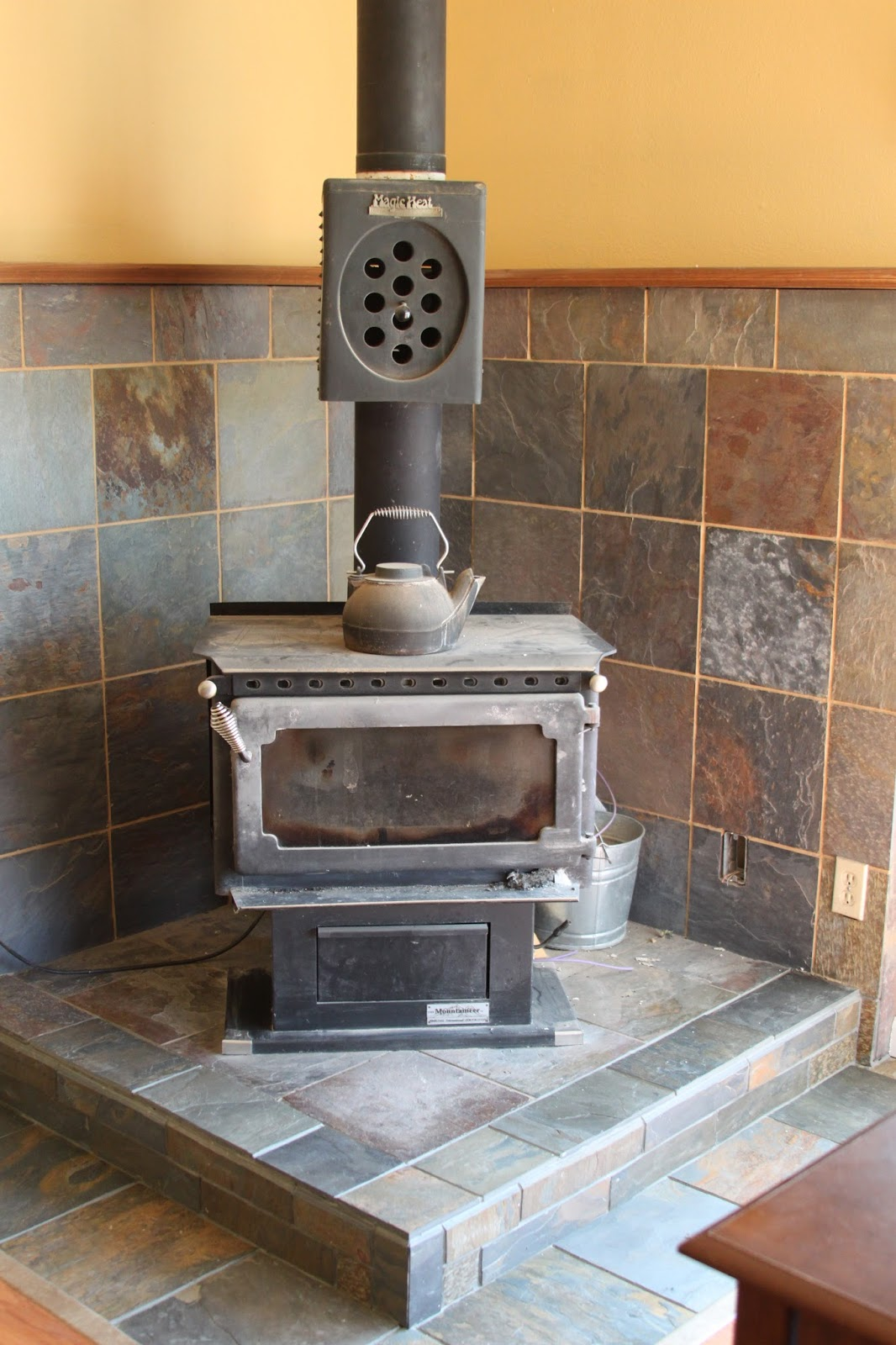 My solution was to cut the edges of the surround tiles at a 45 degree angle  so that it couldn't shear off. We added tiles to the face of the platform  as ... - Li'l Buck's Creations: Wood Stove Slate Tile Surround