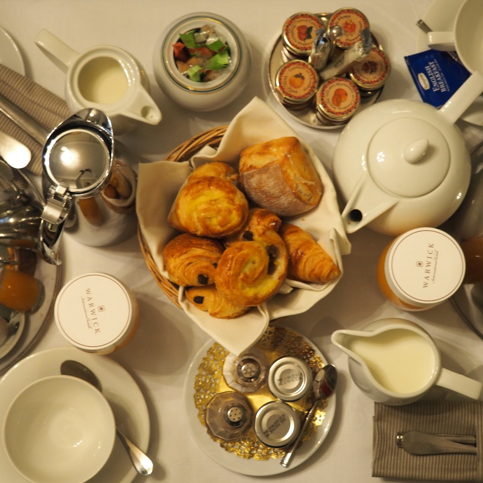 Flatlay of room service breakfast with patisserie in the centre and tea around at hotel westminster, paris