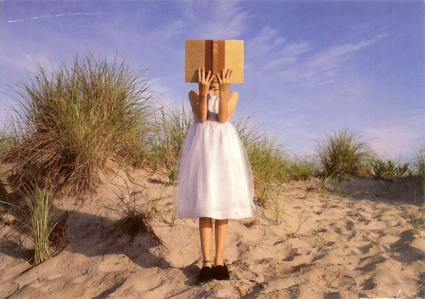 young girl wearing a party dress, standing in sand dunes, reading