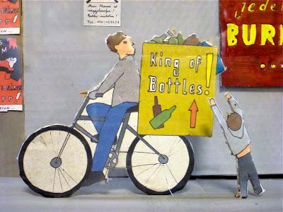 """Aus Pappe ausgeschnitten und bemalt: Mann auf dem Rad, das viele Flaschen transportiert, darauf ein Schild: """"King of the bottles"""""""