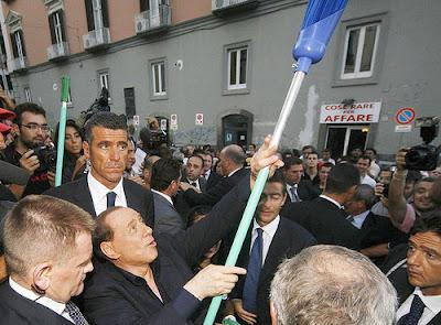 Silvio Berlusconi brandishes a broom in Neaples