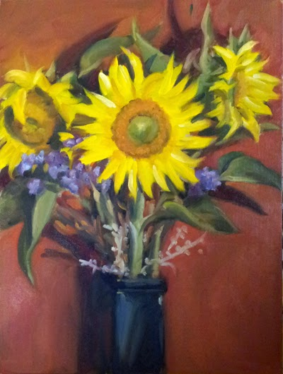 Oil painting of three sunflowers with leaves in a rectangular blue glass vase.