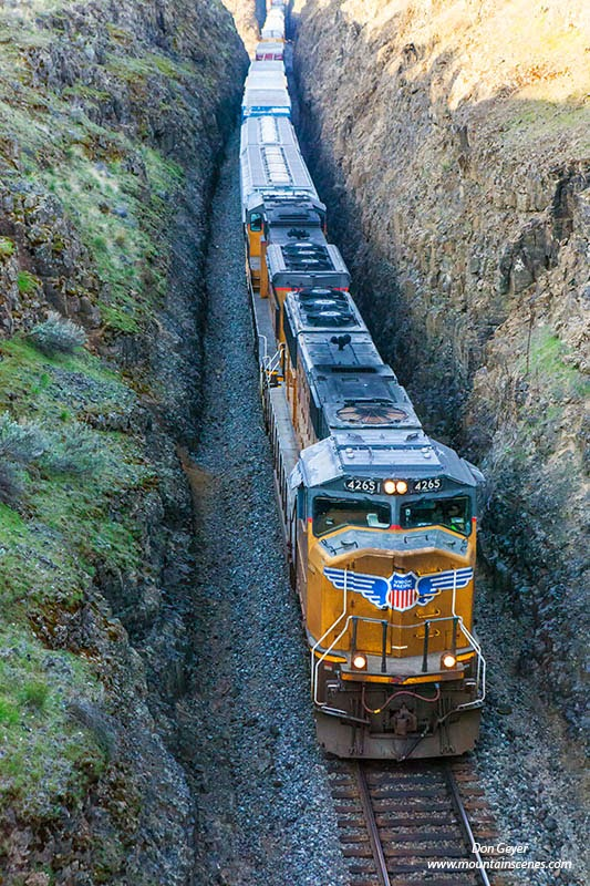 A train passes through a carved out route in the Palouse near Palouse Falls State Park, Washington, USA.
