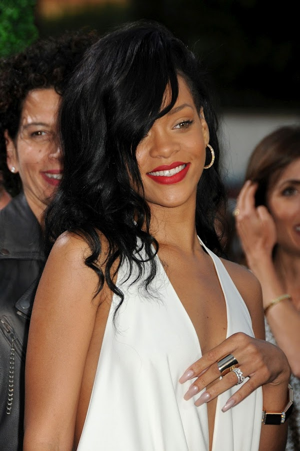 Rihanna smiles for paparazzi in a sexy white dress
