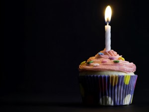 Photo of a cupcake with a single lit candle in the top, against a black background