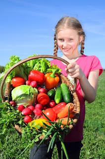 Niña con canasta de vegetales frescos del huerto