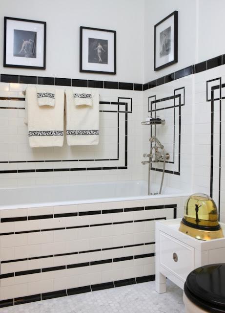Jessica Lagrange's black and white tiled bath tub and white towel holder stand
