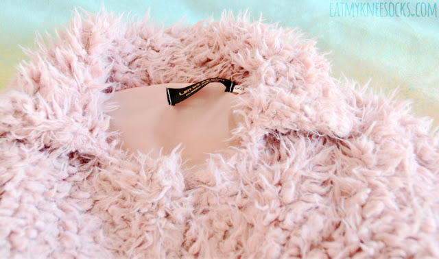 Details on SheIn's dusty light pastel pink faux fur longline coat, which is fully-lined with a silky inner material, featuring long sleeves, ultra-soft fur, a folded collar, and two small hidden hooks in the front.