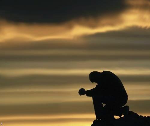 Hình ảnh người đàn ông ngồi trên hòn đá và khóc