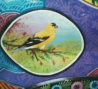 painting of yellow bird scene in a black circle painted onto decorated car