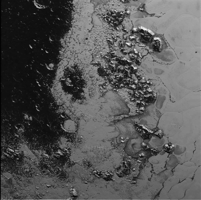 A newly discovered mountain range lies near the southwestern margin of Pluto's heart-shaped Tombaugh Regio (Tombaugh Region), situated between bright, icy plains and dark, heavily-cratered terrain.   This image was acquired by New Horizons' Long Range Reconnaissance Imager (LORRI) on July 14, 2015, from a distance of 48,000 miles (77,000 kilometers) and sent back to Earth on July 20. Features as small as a half-mile (1 kilometer) across are visible.  These frozen peaks are estimated to be one-half mile to one mile (1-1.5 kilometers) high, about the same height as the United States' Appalachian Mountains. The Norgay Montes (Norgay Mountains) discovered by New Horizons on July 15 more closely approximate the height of the taller Rocky Mountains.    The names of features on Pluto have all been given on an informal basis by the New Horizons team.   Credit: NASA/Johns Hopkins University Applied Physics Laboratory/Southwest Research Institute