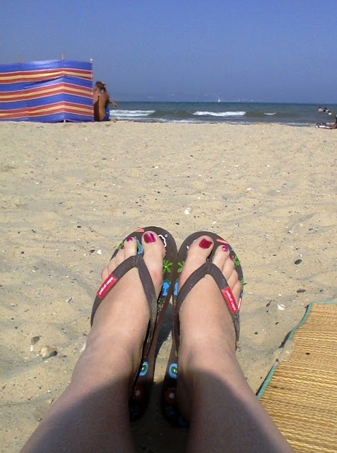 Feet in flip-flops on beach