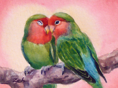 Two colorful lovebirds cuddle on a branch