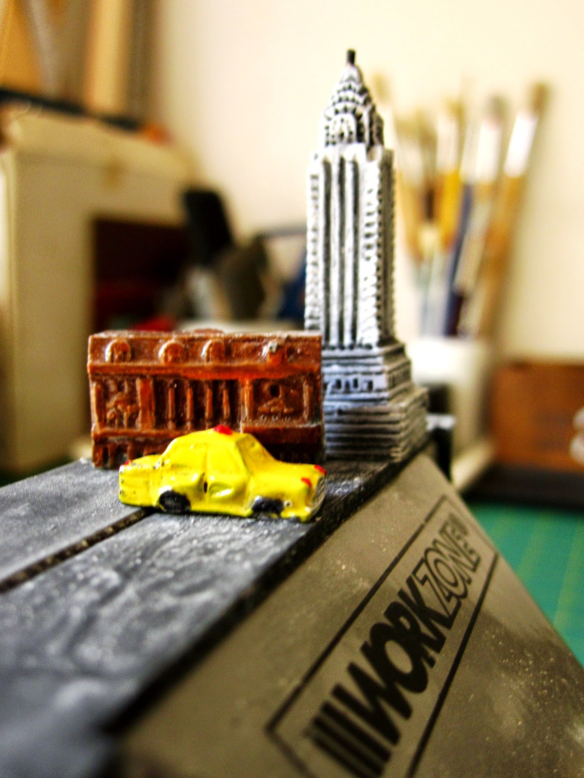 Tiny models of the Chrysler Building, the New York Stock Exchange and a New York yellow cab on top of a table vice.