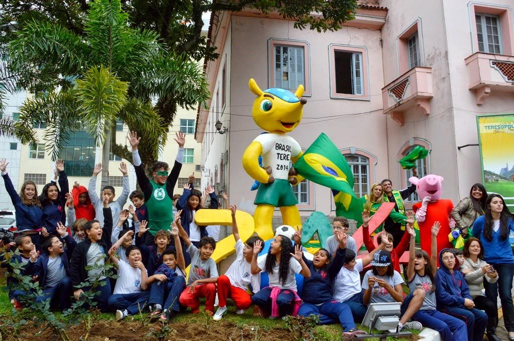 Estudantes posam para fotografia em frente à escultura que enfeita a entrada da Prefeitura de Teresópolis